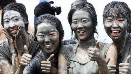 Women pose for photographs during the Boryeong Mud Festival at a beach in Boryeong