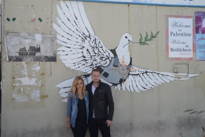 Breaking Borders_Series Premiere_Mariana van Zeller and Michael Voltaggio stand in front of symbolic graffiti art by artist Banksy on the Israeli West Bank barrier