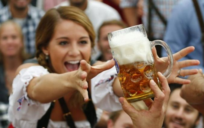 673554-a-visitor-reaches-for-of-the-one-of-the-first-mugs-of-beer-during-opening-ceremony-for-180th-oktober